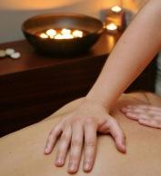 Woman executing massage treatment on man.